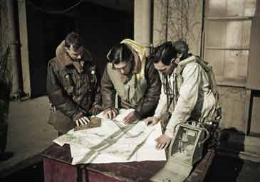 Royal Air Force bomber crew plotting a course on a map before a raid